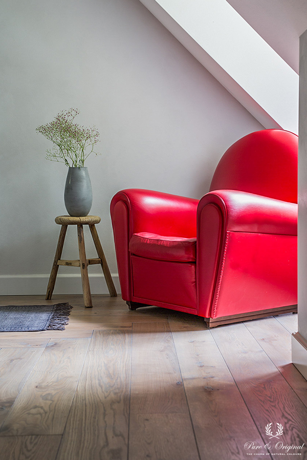 Licetto in the colour Ashes, applied behind the red chair