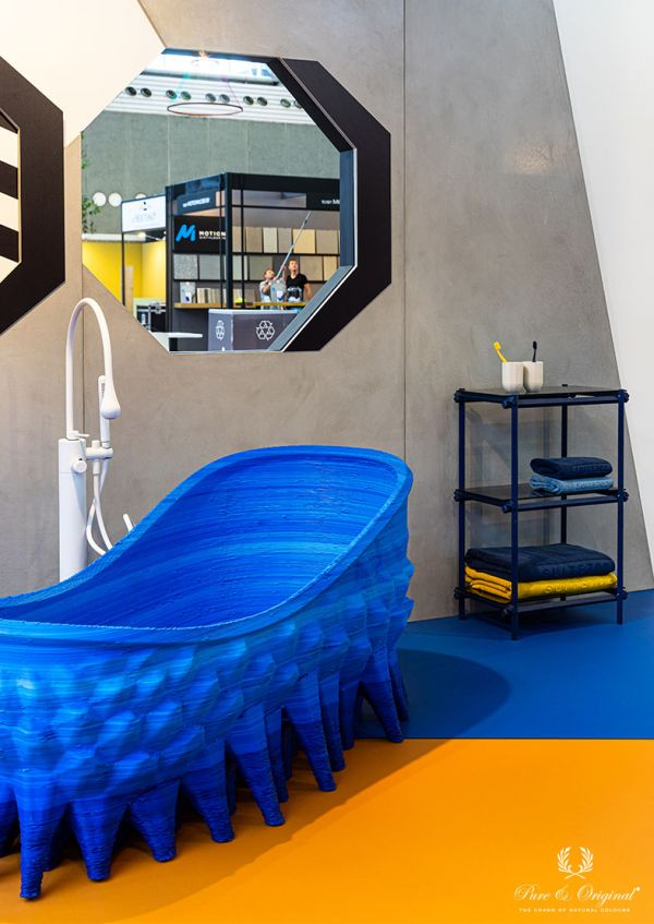 Bathroom with yellow and blue floor, blue 3D printed bathtub, walls painted with white washable wall