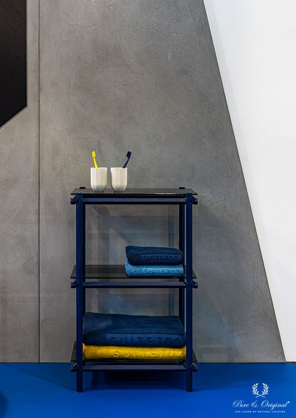 Bathroom with concrete look walls with gloss finish. Bathroom cabinet in blue with glass, yellow and